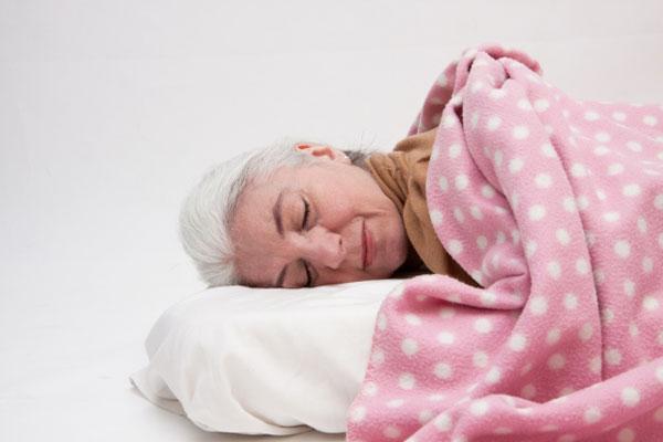 毛布をかぶって眠る女性